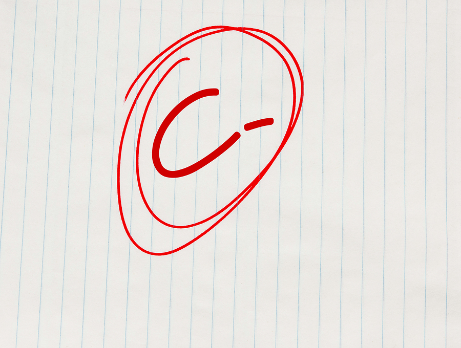 C minus (C-) grade written in red on notebook paper